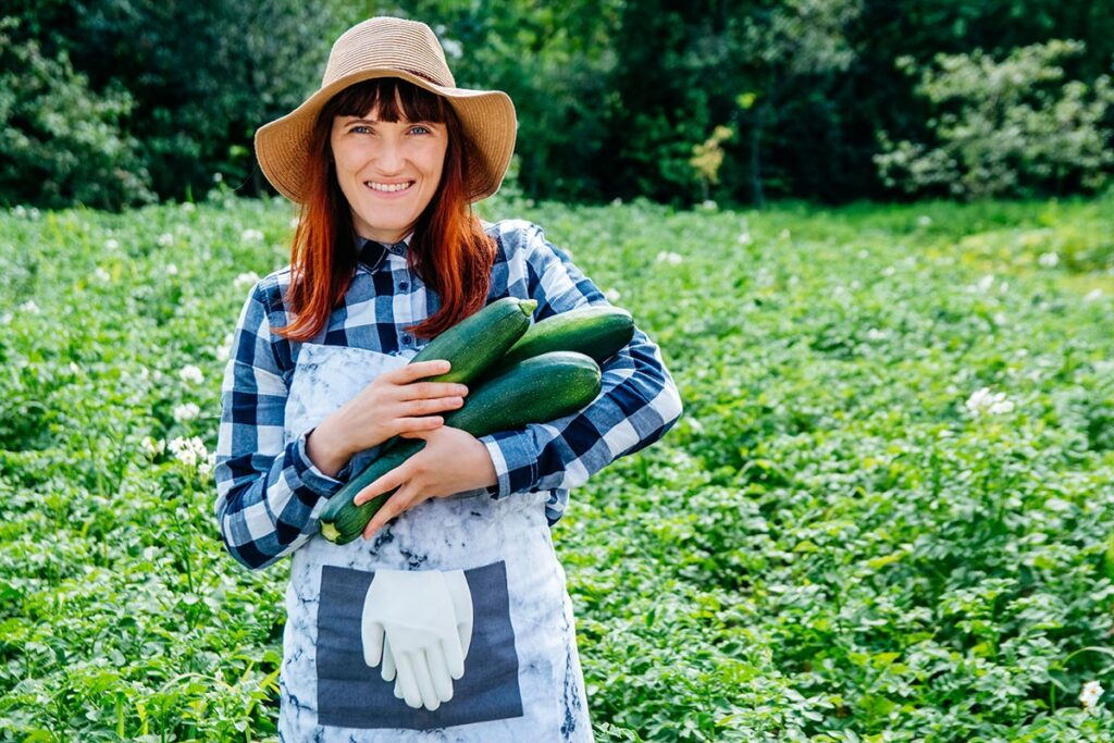 8 Reasons to Adopt a Plant-Based Diet, woman in apron and sunhat holding a bunch of harvested zucchini